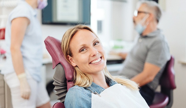 A woman smiling while sitting in the dentist's chair and the dentist and dental hygienist speak in the background