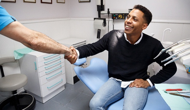 A young man shaking the hand of a dentist