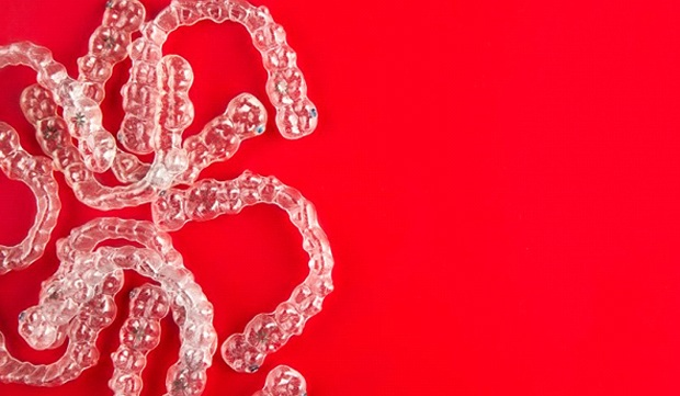 Invisalign clear braces on red background